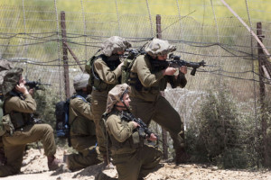 Israeli soldiers keep their position along Israel's border with Syria as demonstrators trying to head into the Israeli-annexed Golan Heights gather on the other side of the fence, as seen from the Druze village of Majdal Shams, on June 5, 2011 as Israeli troops opened fire at protestors from Syria who stormed a ceasefire line in the occupied Golan Heights, killing three demonstrators, according to Syrian television. AFP PHOTO/MENAHEM KAHANA